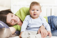 Happy family: Joyous mother and baby boy sitting in bed. Adorable joyful baby boy sitting in bed next to his mother while she is embracing him lying down and Royalty Free Stock Photos