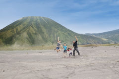 Happy family jump on volcanic desert 1. Joyful family jump on volcanic desert, shot outdoors Stock Image