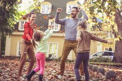 Happy family jumping at backyard. Fall leaves is fun. Happy family royalty free stock photo