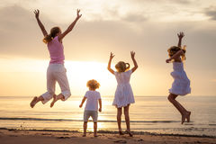 Happy family jumping on the beach Stock Photos