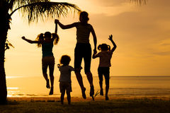 Happy family jumping on the beach Stock Photography