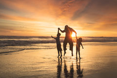 Happy family jumping on beach Stock Images