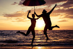 Happy family jumping on the beach at the sunset time. Stock Photos