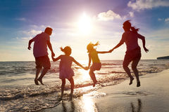 Happy family jumping on the beach. Happy family jumping together on the beach royalty free stock photo