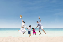 Happy family jumping at beach Stock Photography