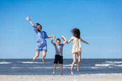 Happy family jumping high on the seashore. stock photography