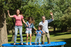 Happy family jumping high on trampoline in park Stock Images