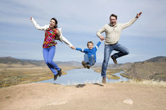 Happy family jumping on the mountain. Happy father and mother with son jumping on the mountain with lake in the background Royalty Free Stock Images