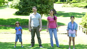 Happy family jumping in the park Stock Images