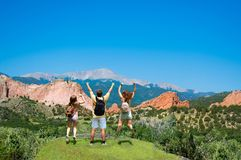 Happy family jumping with raised hands on vacation hiking trip. Beautiful red mountains and green hills in Colorado. Garden of the Gods, Colorado Springs stock photography