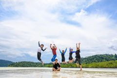 Happy family jumping together on the beach, Thailand. Asian traveler group adult and teens are family, Happy life enjoy by play jumping together at the beach on stock photography