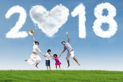Happy family under numbers 2018. Happy family jumping together under clouds shaped numbers 2018 and heart. Shot in the meadow stock photos