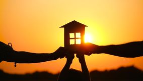 A happy family keeps a paper house on the background of a beautiful sunset. The concept of family relationships, love. And real estate. Close-up hands stock video footage