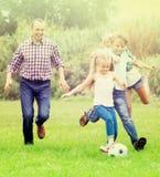 Happy family kicking the ball Stock Image