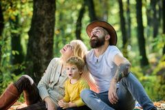 Happy family with kid boy relaxing while hiking in forest. Family weekend. Mother father and little son sit forest royalty free stock photography