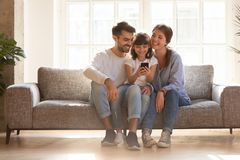 Happy family and kid having fun with smartphone at home. Happy family and kid daughter having fun with smartphone gadget at home, little child girl looking at royalty free stock photo
