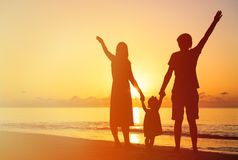 Happy family with kid having fun on sunset beach Stock Photo