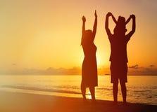Happy family with kid having fun on sunset beach Stock Photo