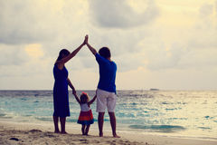 Happy family with kid having fun on sunset beach Royalty Free Stock Images