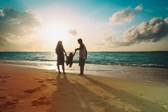 Happy family with kid play on sunset beach. Vacation royalty free stock photo