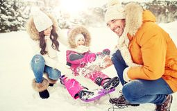 Happy family with kid on sled having fun outdoors. Parenthood, fashion, season and people concept - happy family with child on sled having fun outdoors Royalty Free Stock Photography