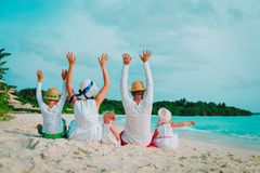 Happy family with kids hands up on beach. Vacation stock photos
