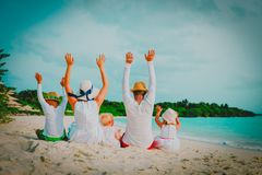 Happy family with kids hands up on beach. Vacation stock image