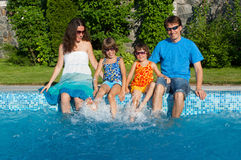 Happy family with kids having fun near pool on vacation Stock Photo