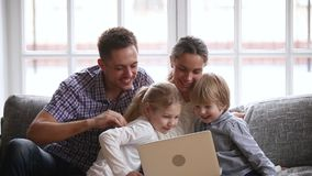 Happy family with kids having fun using laptop together stock footage