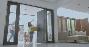 Happy family with kids holding boxes entering new modern house. Family relocating concept stock footage