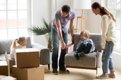 Happy family with kids playing on moving day at home. Happy young family with small kids having fun together playing on moving day in new home concept, father Stock Images
