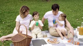 Happy family with kids resting on the grass during a picnic. Happy family with kids resting on the grass during a picnic stock footage