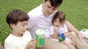 Happy family with kids resting on the grass during a picnic. Happiness and harmony in family life. Happy family with kids resting on the grass during a picnic stock footage