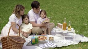 Happy family with kids resting on the grass during a picnic. Happiness and harmony in family life. Happy family with kids resting on the grass during a picnic stock video
