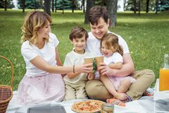 Happy family with kids resting on the grass during a picnic. Happiness and harmony in family life stock photo