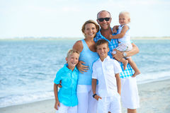Happy family with kids standing on the beach. Stock Images