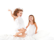 Happy family .  kids twin sisters jumping on the bed, playing an. Happy family at home. kids twin sisters jumping on the bed, playing and laughing Royalty Free Stock Images