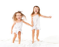 Happy family .  kids twin sisters jumping on the bed, playing an Stock Images