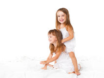 Happy family .  kids twin sisters jumping on the bed, playing an. Happy family at home. kids twin sisters jumping on the bed, playing and laughing Royalty Free Stock Photography
