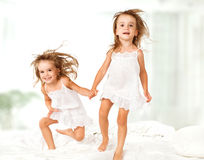 Happy family .  kids twin sisters jumping on the bed, playing and laughing. Happy family at home. kids twin sisters jumping on the bed, playing and laughing Stock Photography
