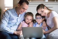 Happy family with kids watching funny video on computer screen stock photos