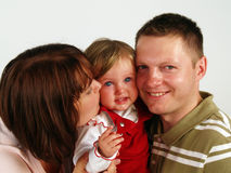 Happy family kiss. Happy family portrait with mother kissing adorable baby Stock Images