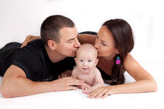 Happy family kiss - mother, father and baby. On a white background Stock Images