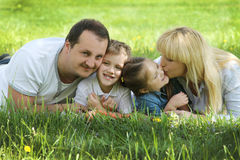 Happy family kissing kids over green Stock Images