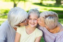 Happy family kissing little girl stock photo