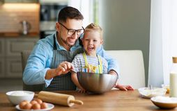Happy family in kitchen. father and child baking cookies royalty free stock photo
