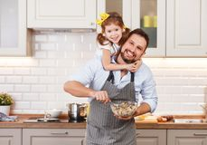 Happy family in kitchen. Father and child daughter knead dough a Stock Images