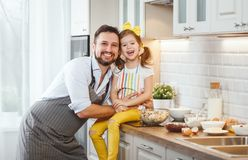 Happy family in kitchen. Father and child daughter knead dough a Royalty Free Stock Photo