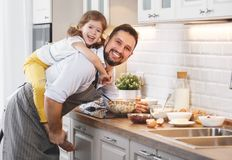 Happy family in kitchen. Father and child daughter knead dough a Royalty Free Stock Photography