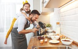 Happy family in kitchen. Father and child daughter knead dough a Stock Photo